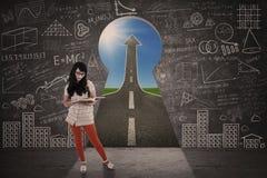 Asiatische Mädchenstudie vor Schlüssellocherfolgsstraße Lizenzfreie Stockfotografie