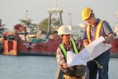 Asiatische männliche Architekten mit dem Plan, der an der Baustelle mit Sicherheit arbeitet stockbild