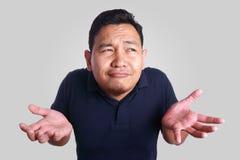 Asiatische Mann-Achselzucken-Geste Stockfotos