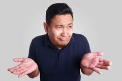 Asiatische Mann-Achselzucken-Geste Stockfotografie