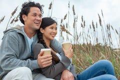 Asiatische Mann-Frauen-romantische Paare, die zum Mitnehmen Kaffee auf Strand trinken lizenzfreie stockfotos