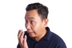 Asiatische Mann-Kontrolle sein eigener Mund-Geruch stockfotos