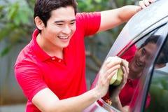 Asiatische Mannreinigung und Reinigungsauto Stockbild