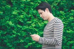Asiatische Mannstellung und mit Smartphone stockfotografie