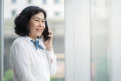 Asiatische mittlere Geschäftsfrau nennen lizenzfreies stockbild
