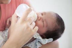 Asiatische Mutter, die ihr neugeborenes Baby mit Milchflasche einzieht Stockfotografie