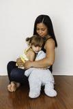 Asiatische Mutter, die ihre 3-jährige Tochter streichelt Stockbild
