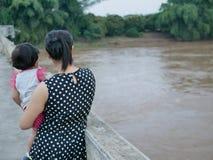 Asiatische Mutter, die ihre kleine Tochterstellung auf einer Brücke achtern zeigt ihrem kleinen Baby einen düsteren schlammigen F stockfoto