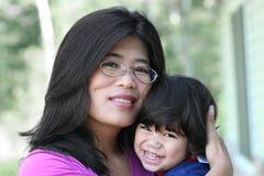 Asiatische Mutter, die liebevoll ihren Sohn anhält Stockfotos
