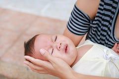 Asiatische Mutter, die schreiendes neugeborenes Baby hält lizenzfreie stockbilder