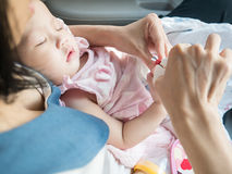 Asiatische Mutter schnitt die Nägel ihres Babys während Babyschlaf Stockfoto