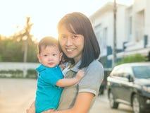 Asiatische Mutter tragen Baby Morgen des Dorfs am im Freien Stockfotografie