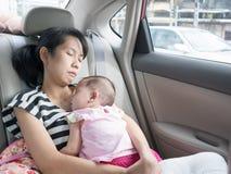 Asiatische Mutter und Baby, die im Auto auf Straße schläft Lizenzfreies Stockbild