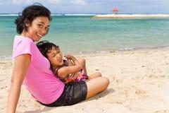 Asiatische Mutter- und des Kindesglückliche Ferien auf dem Strand stockfotos