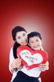 Asiatische Mutter und Sohn, die Liebeskarte auf Rot hält lizenzfreie stockbilder