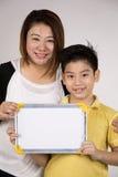 Asiatische Mutter und Sohn mit leerer weißes Brett- und schauenkamera Lizenzfreie Stockbilder