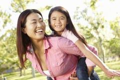 Asiatische Mutter und Tochter des Porträts, die im Park spielt Stockfotografie
