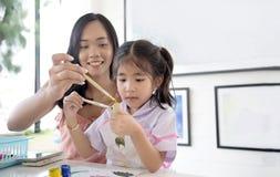 Asiatische Mutter- und Tochtermalereiwasserfarbe lizenzfreie stockbilder