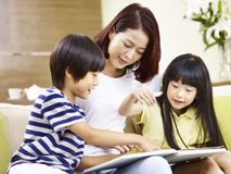 Asiatische Mutter und zwei Kinder, die zu Hause ein Buch lesen Lizenzfreie Stockfotos
