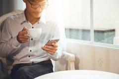 Asiatische Nationalität des Geschäftsmannes, die am Kaffee sitzt lizenzfreie stockfotografie