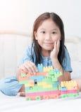 Asiatische nette Mädchenspiel-Blockziegelsteine auf Bett Stockbild