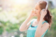 Asiatische nette schöne jugendlich hörende Musik mit drahtlosem Kopfhörer lizenzfreies stockbild