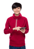 Asiatische Note des jungen Mannes am Handy Stockbild