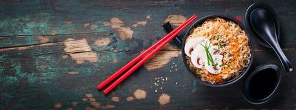Asiatische Nudeln mit Gemüse und Pilzen, Sojasoße, Stöcke auf einem dunklen Hintergrund Lizenzfreies Stockfoto
