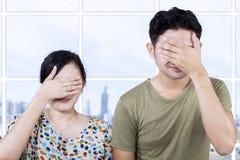 Asiatische Paarabdeckungsgesichter in der Wohnung Lizenzfreie Stockbilder