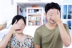 Asiatische Paarabdeckungsgesichter zu Hause Stockfotografie