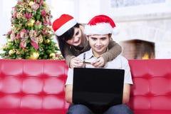 Asiatische Paare in den Weihnachtshüten, die online kaufen Lizenzfreies Stockbild