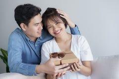 Asiatische Paare der glücklichen jungen Liebe, die zu Hause auf der Couch betrachtet ein Geschenkboxbraun sitzen lizenzfreie stockfotografie