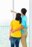 Asiatische Paare, die aus Wohnungsfenster heraus schauen Lizenzfreie Stockfotografie