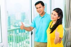 Asiatische Paare, die aus Wohnungsfenster heraus schauen Lizenzfreie Stockbilder