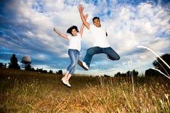 Asiatische Paare, die für Freude springen Stockbild