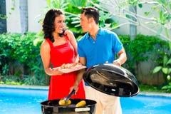 Asiatische Paare, die Grill am Pool haben stockfotos