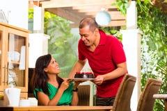 Asiatische Paare, die Kaffee im Wohnzimmer trinken Stockbild