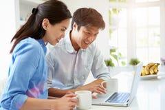 Asiatische Paare, die Laptop in der Küche betrachten Stockfotos