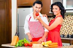 Asiatische Paare, die Lebensmittel in der inländischen Küche zubereiten Stockfotos