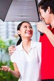 Asiatische Paare, die mit Regenschirm durch Regen gehen Lizenzfreies Stockbild