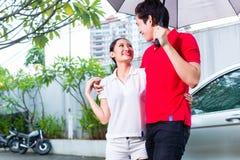 Asiatische Paare, die mit Regenschirm durch Regen gehen Lizenzfreies Stockfoto