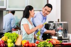 Asiatische Paare, die zusammen Lebensmittel in der Küche kochen Lizenzfreie Stockfotografie