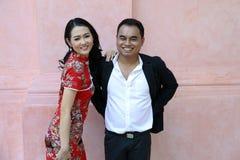 Asiatische Paare im Kleid der chinesischen Art lächeln und stehen agianst Rosawand Lizenzfreie Stockfotografie