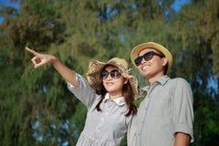Asiatische Paare zeigen ihre Finger auf den Strand auf Sommerzeit, sind die Männer und Frauen, die Sonnenbrille tragen, betrachte stockfotos