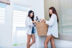 Asiatische Paarfrauen, die zusammen Hausarbeit und Aufgaben vor Waschmaschine tun und Kleidung und in der Waschk?che laden Leute lizenzfreie stockfotos