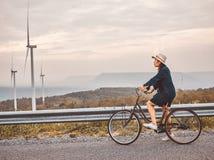 Asiatische Reisendfrau im Baumwollstoffkleid mit klassischer Fahrradstra?e in der Retro- zeitgen?ssischen Art lizenzfreie stockfotografie