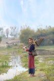 Asiatische schöne Dame im Stammkleiderstand nahe Sumpf mit fishin stockbild