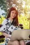 Asiatische schöne junge Frau, die auf der Bank mit Laptop sitzt stockfotografie