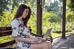 Asiatische schöne junge Frau, die auf der Bank mit Laptop sitzt lizenzfreies stockbild