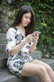 Asiatische schöne junge Frau, die mit intelligentem Telefon spielt lizenzfreie stockbilder